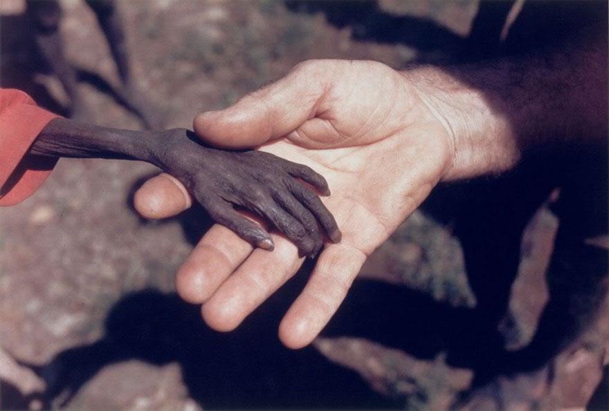 Näljane laps hoiab käest kinni vabatahtlikul, kes neid aitama läks